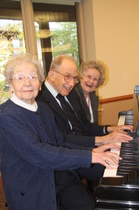 (L to R) Alice Cohen, Lionel Ruberg, and Peggy Ritter sit at one of Pennswood's pianos